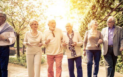 Group of older people walking in park